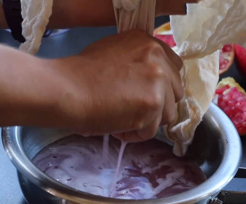Closeup of hands squeezing the pomegranate juice from the seeds wrapped in cheesecloth into a pot below.