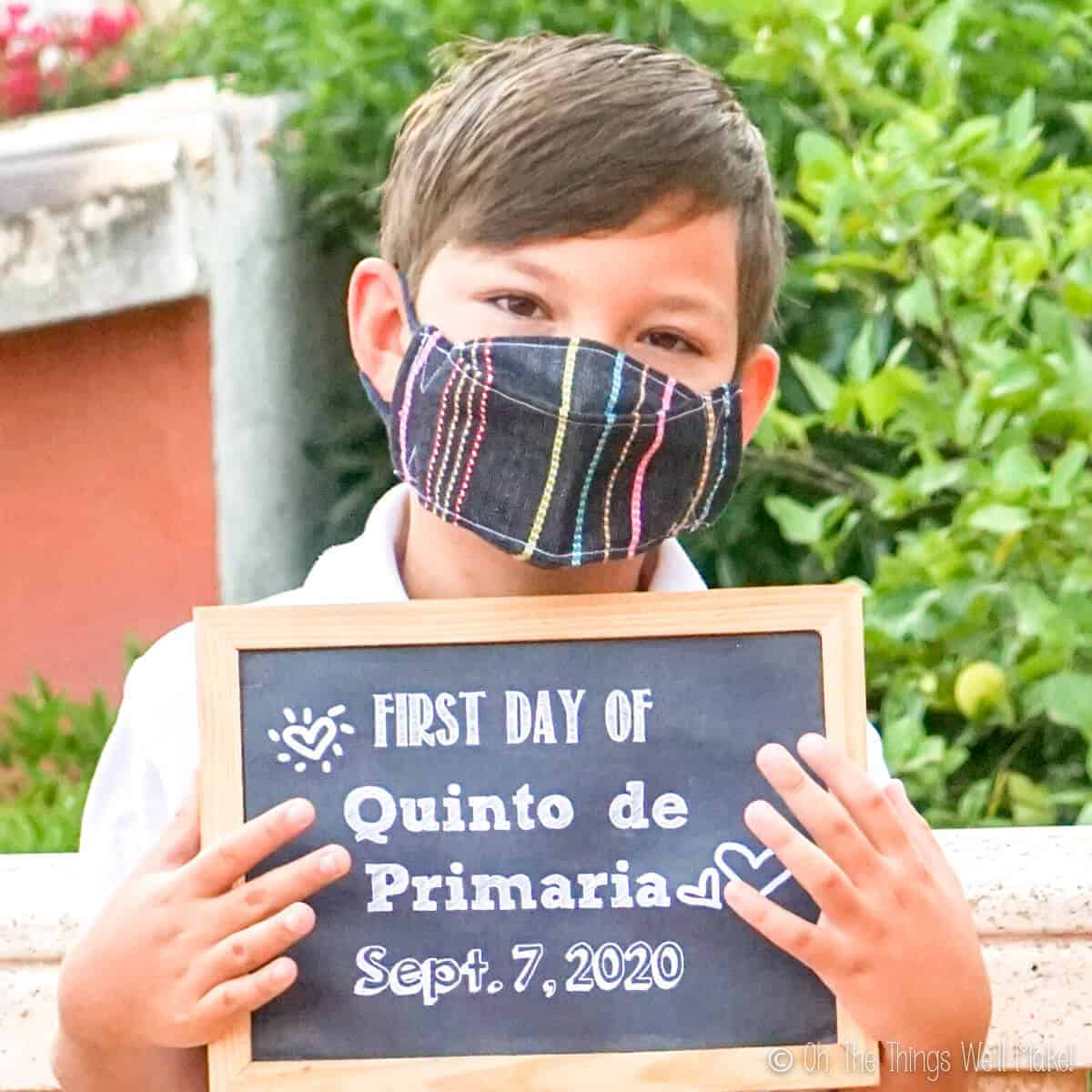 A boy wearing a face mask and holding a first day of school sign