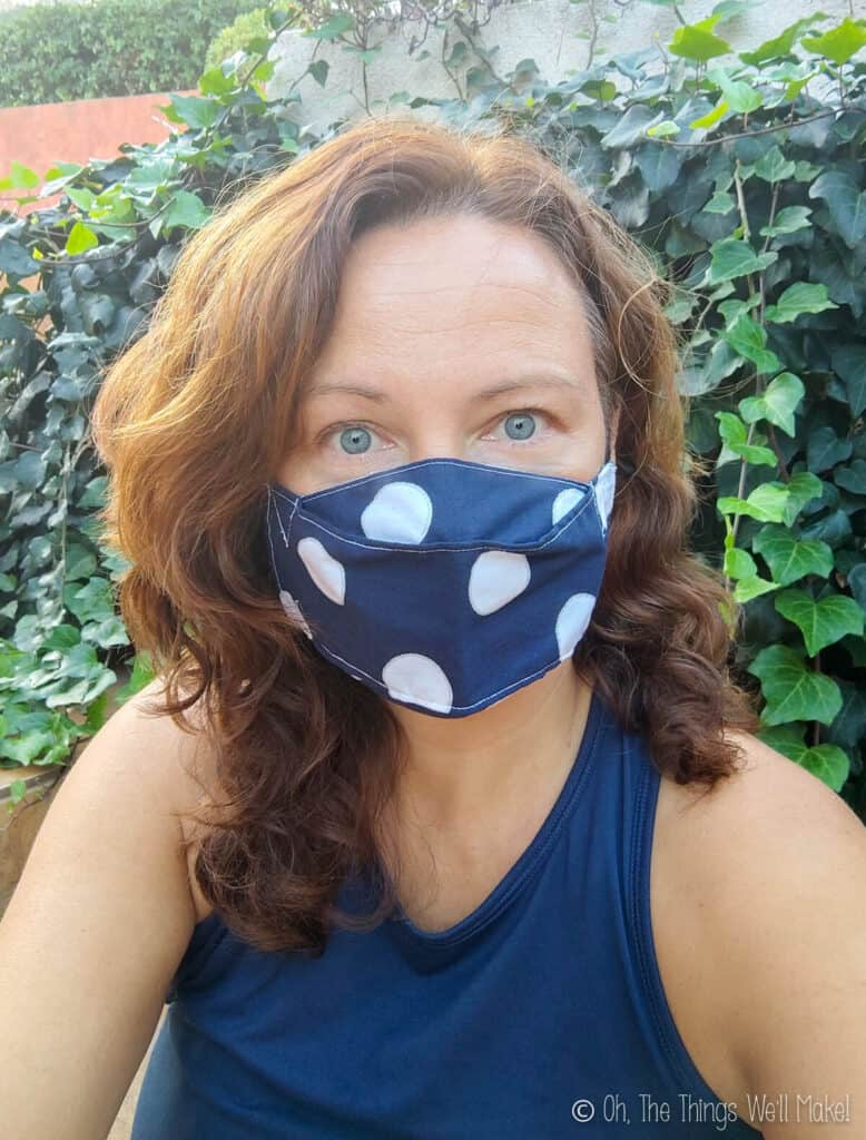 A woman wearing a navy blue and white polka dotted mask