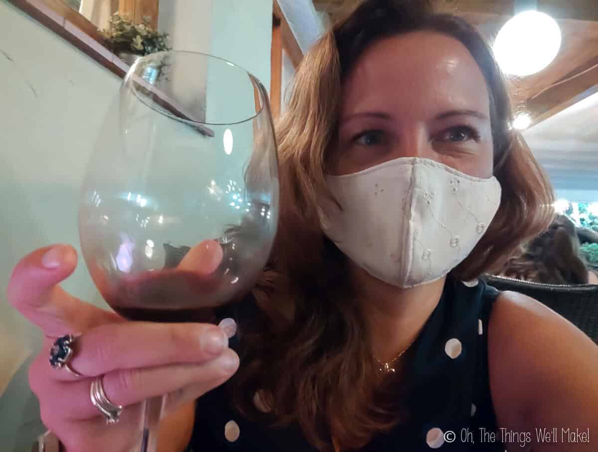 A woman wearing a mask and holding up a glass of red wine.