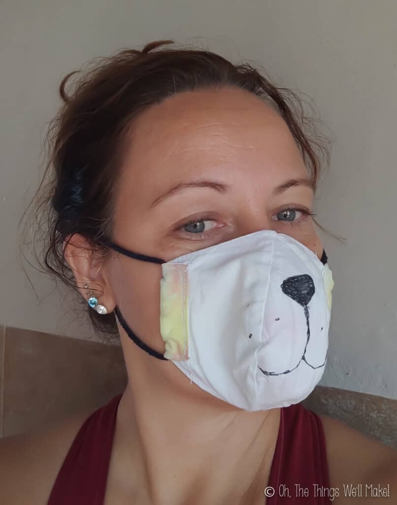 A woman wearing a face mask with an animal face drawn on it.