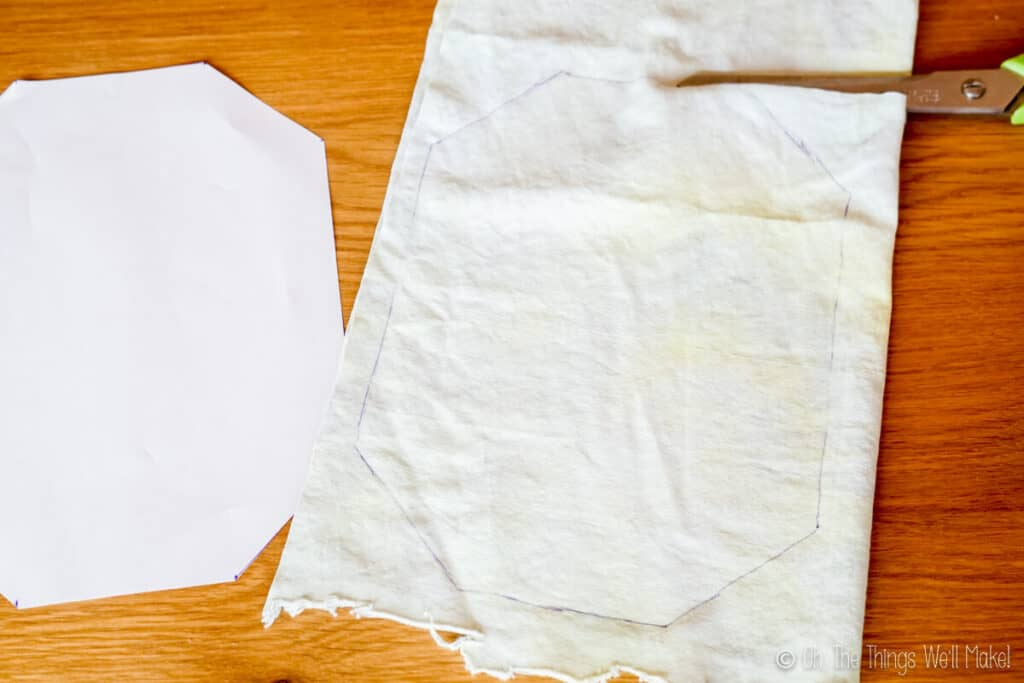 Overhead view of a piece of fabric with an oblong octogon pattern drawn on it