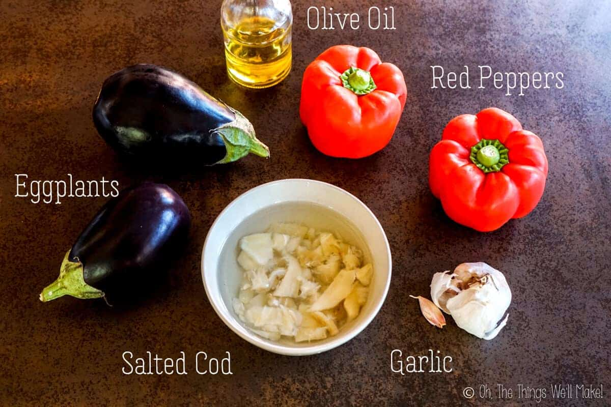 Overhead view of the ingredients for espencat: red peppers, eggplants, salted cod, olive oil, and garlic