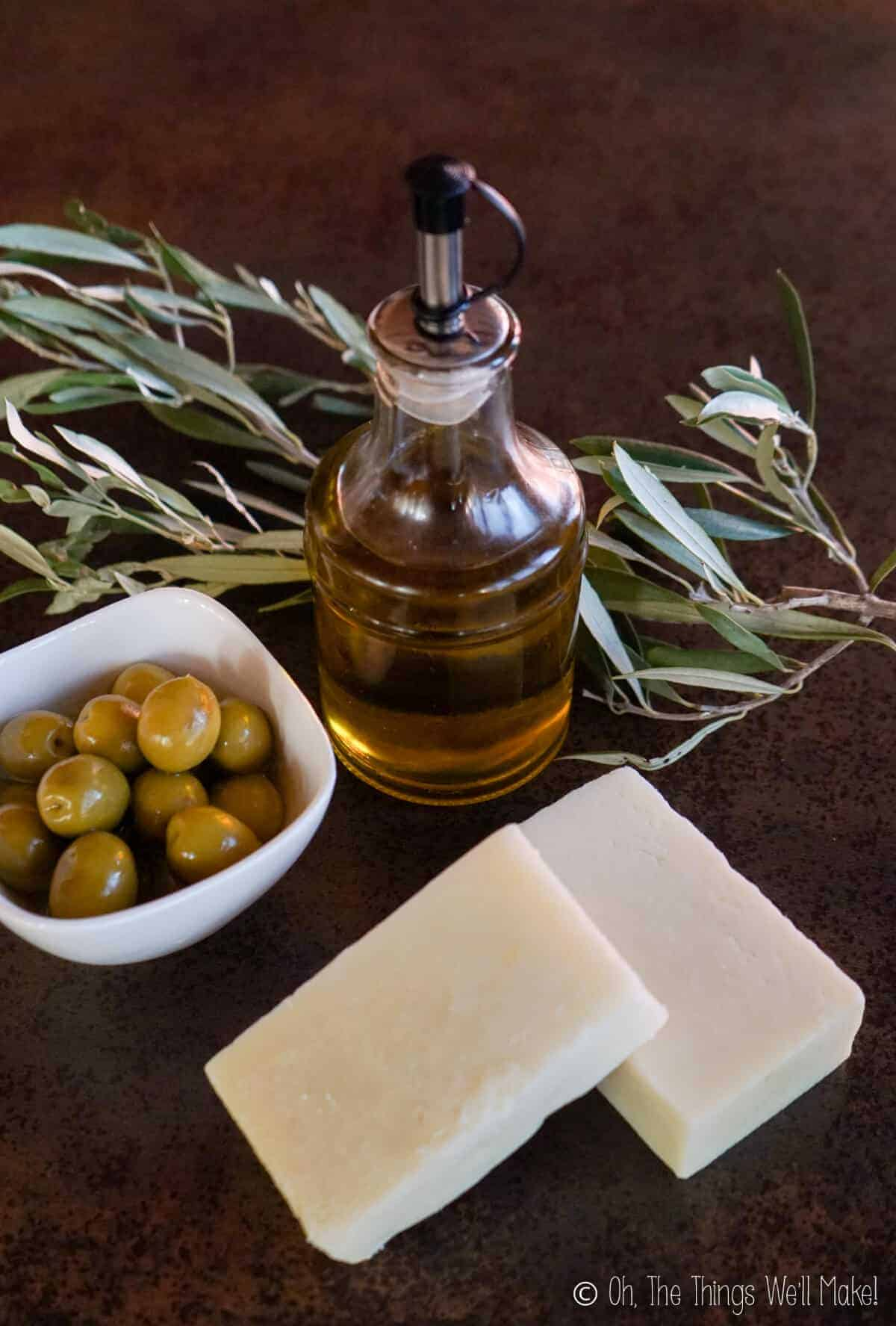 Olive oil in a bottle near a bowl of olives and 2 bars of Castile soap
