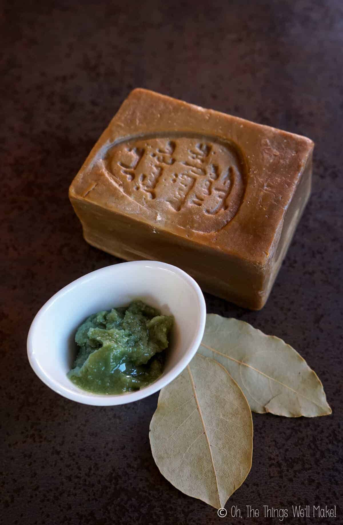 Overhead view of a small container with laurel berry oil next to some bay leaves and a bar of Aleppo soap