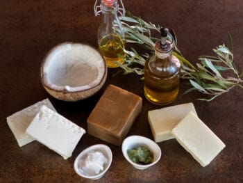 Several oils in bottles and bowls near some homemade soaps
