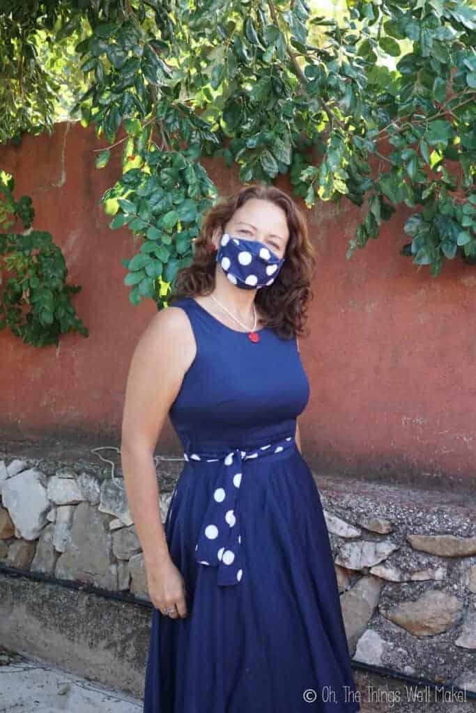a girl wearing a polka dot face mask with matching sash