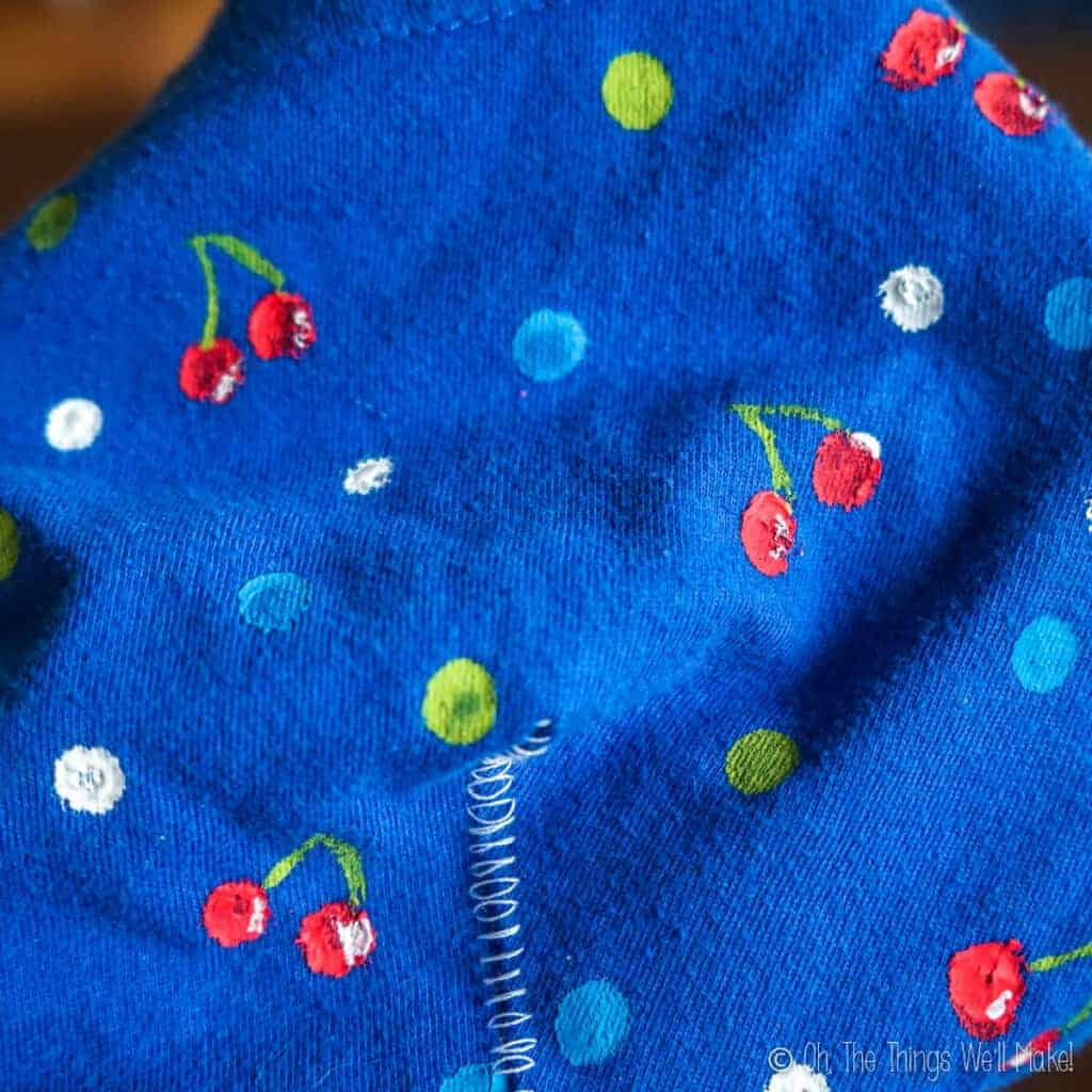 Closeup of cherries and polka dots painted onto a blue fabric
