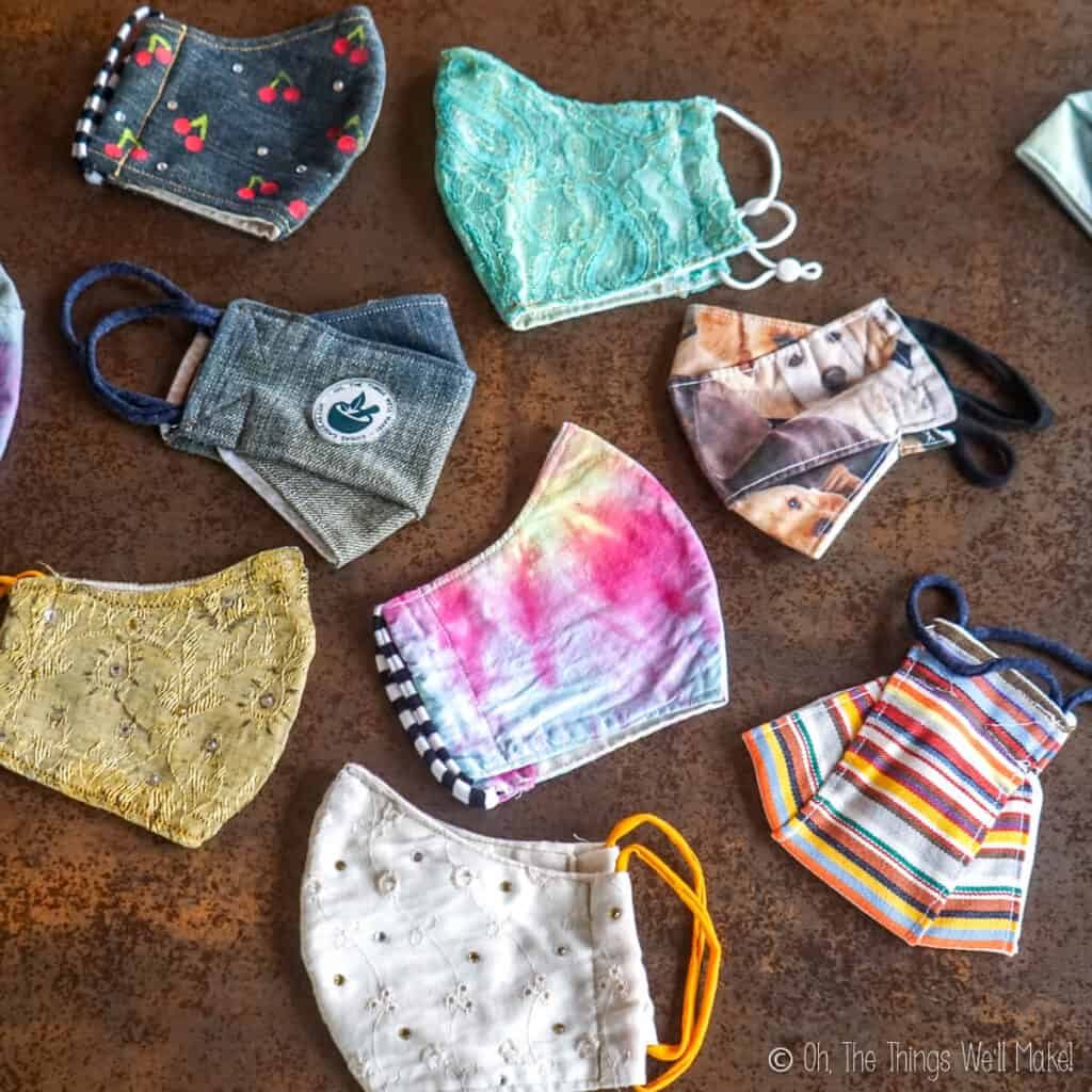 Overhead view of a variety of fun face masks, tie dyed masks, denim masks, lace masks, etc.