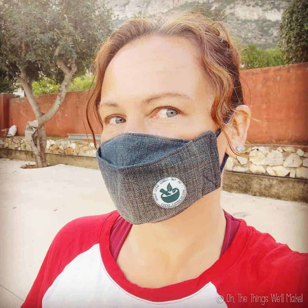 Tracy wearing a denim mask with her blog logo pinned onto it.