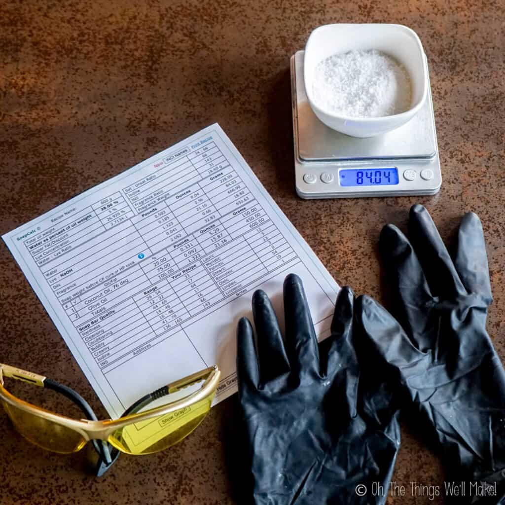 Overhead view of.a soap recipe as printed from a lye calculator. Next to the recipe are some gloves, safety glasses, and a bowl with lye in it.