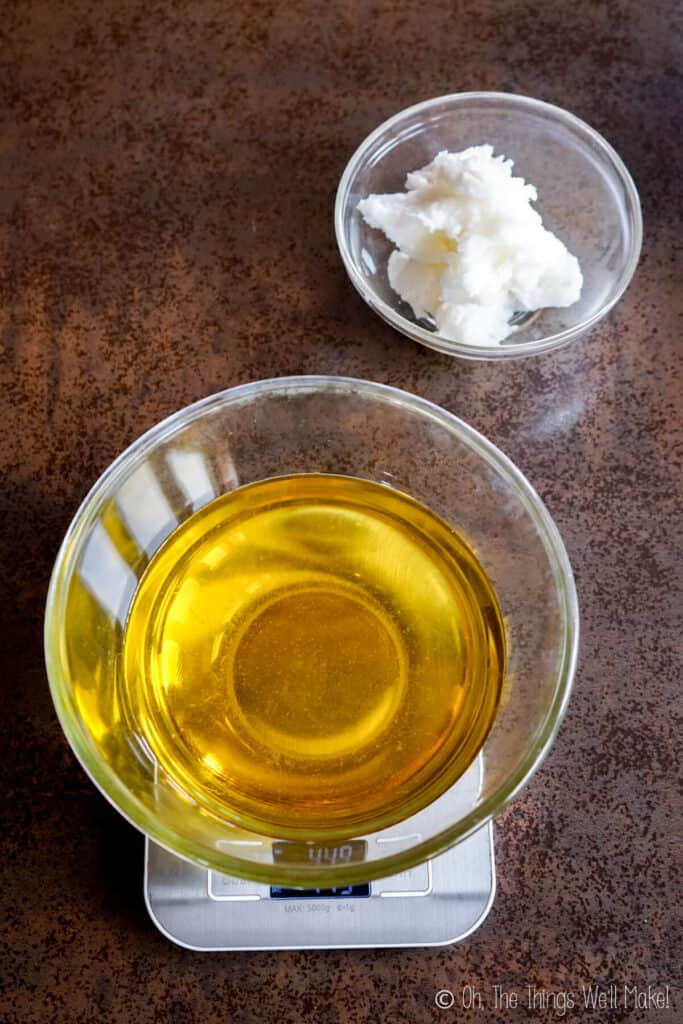 A bowl of solid coconut oil next to a bowl filled with olive oil on a scale.