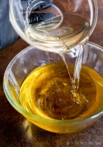 Pouring coconut oil into a bowl with olive oil.
