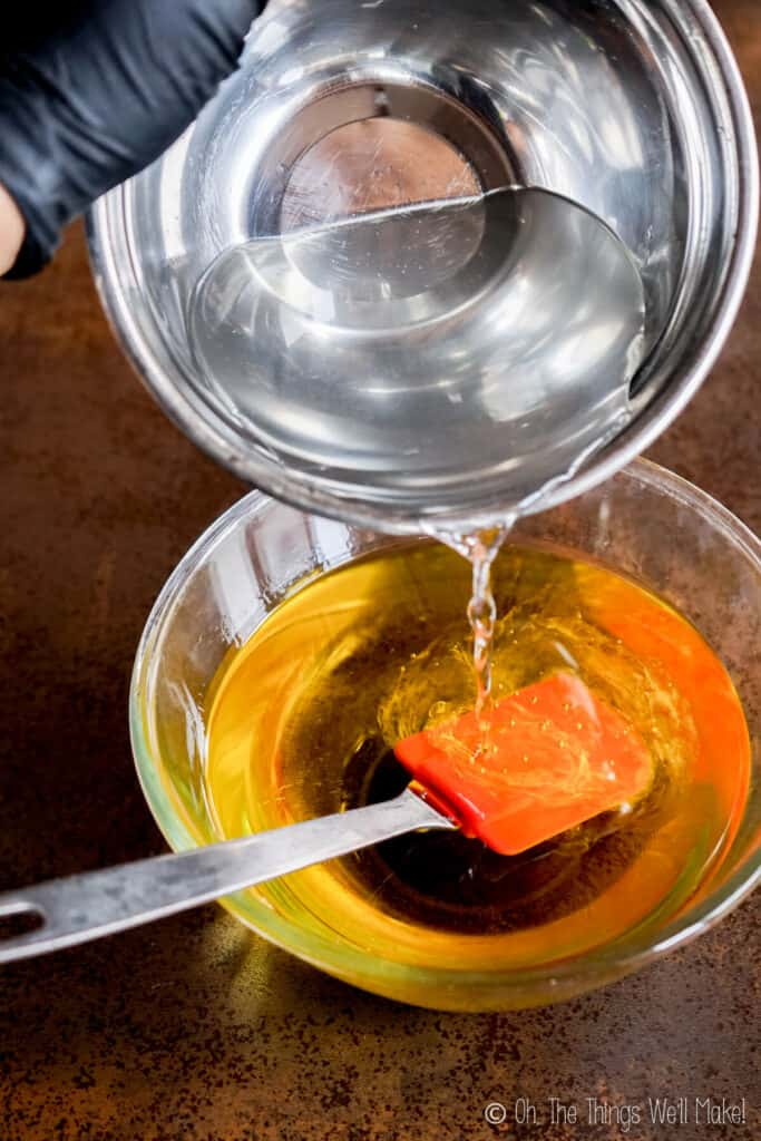 Pouring a lye solution into a bowl with oil