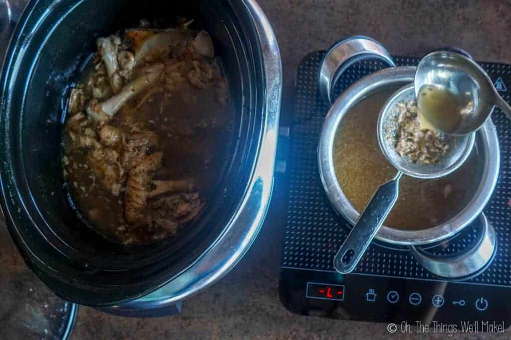 Straining turkey stock into a small pot next to the slow cooker