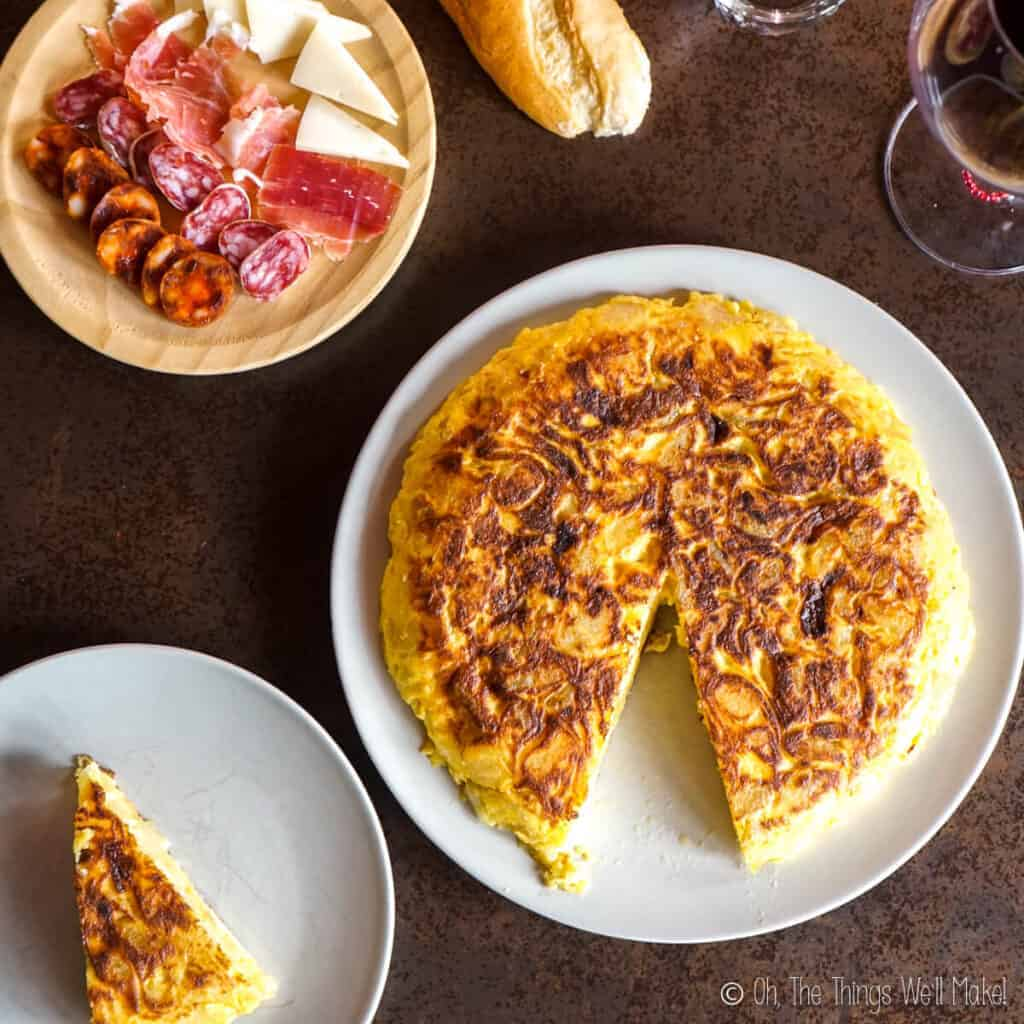Overhead view of a Spanish tortilla on a plate next to a smaller plate with one slice of the tortilla on it and other plate with ham, cheese, and chorizo.