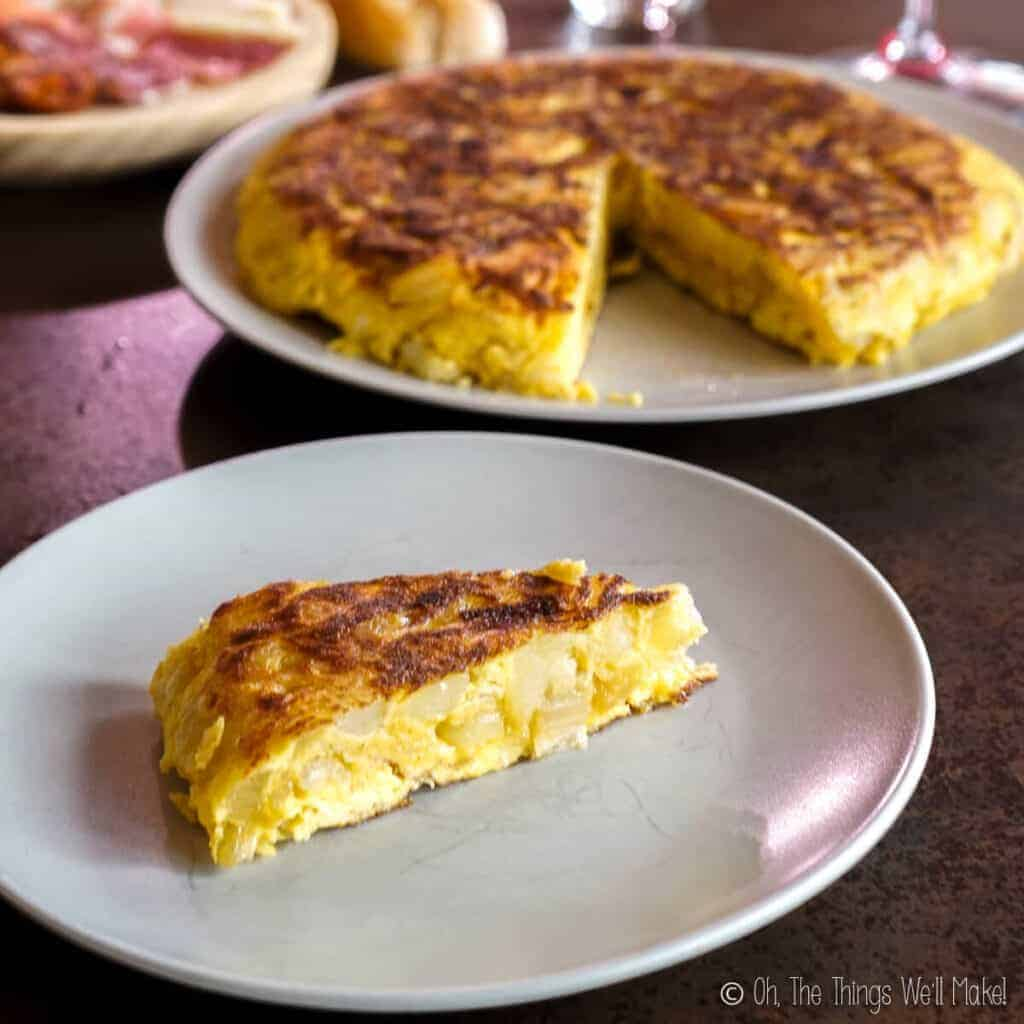 A slice of Spanish tortilla that is slightly uncooked in the center.