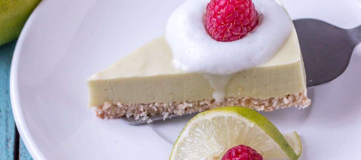 Overhead view of a slice of a paleo key lime pie garnished with coconut cream and a raspberry being placed on a white plate with a silver spatula next to a slice of lime and a raspberry.