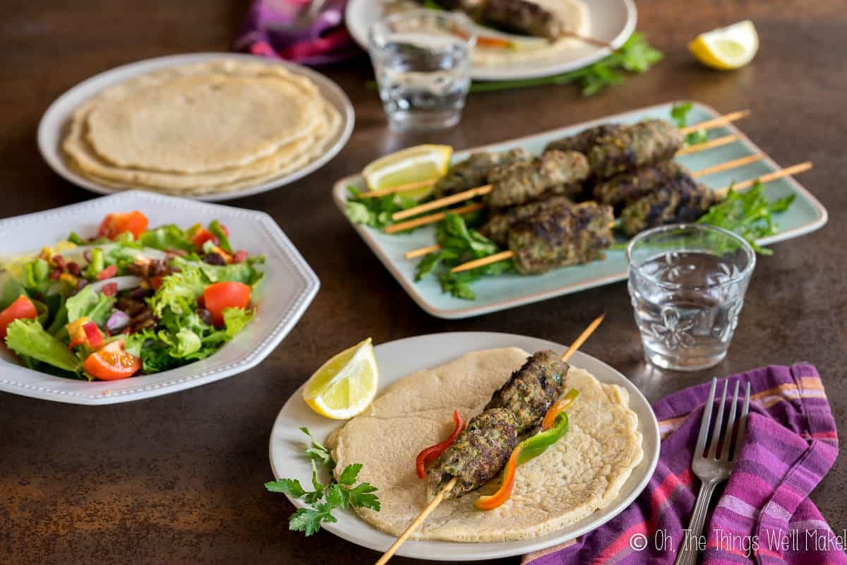 A beef kafta kebab on a pita in front of a stack of cooked kafta.