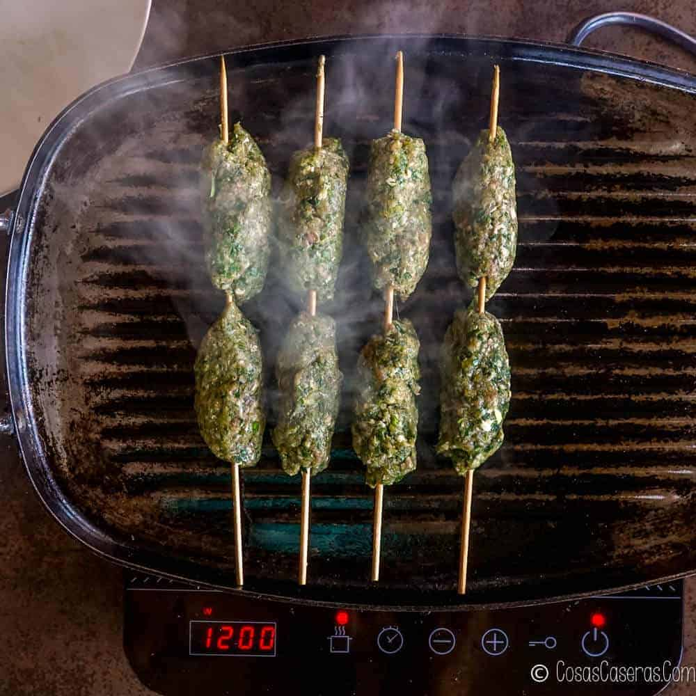 Grilling kafta on a grill skillet