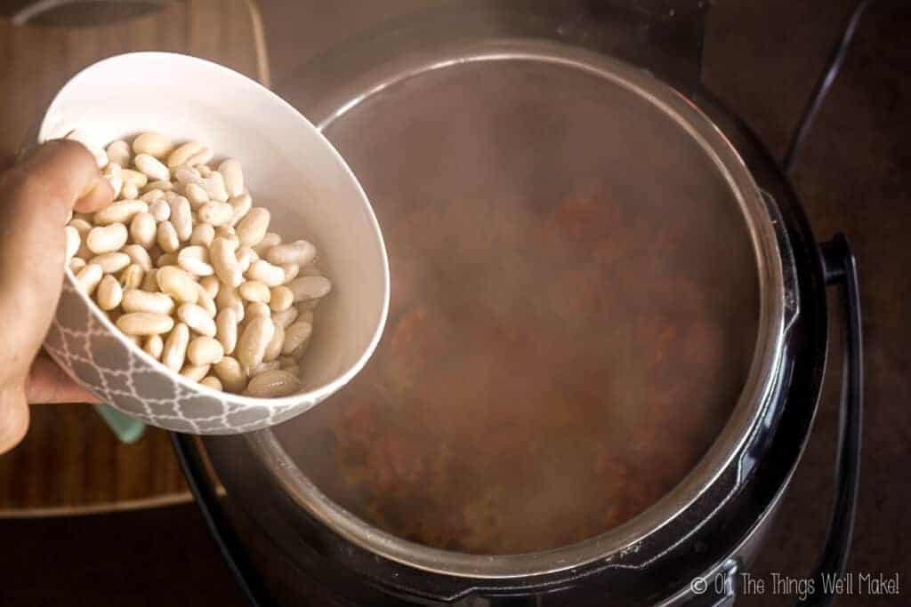Pouring the soaked beans into the pressure cooker