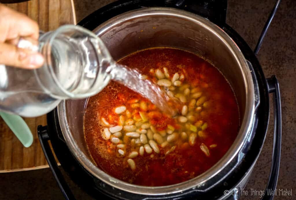 Pouring water over the beans in the pressure cooker