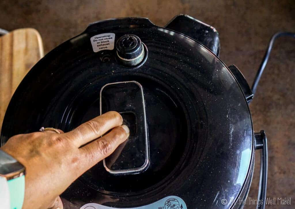 Pressing the steam release valve of a slow cooker