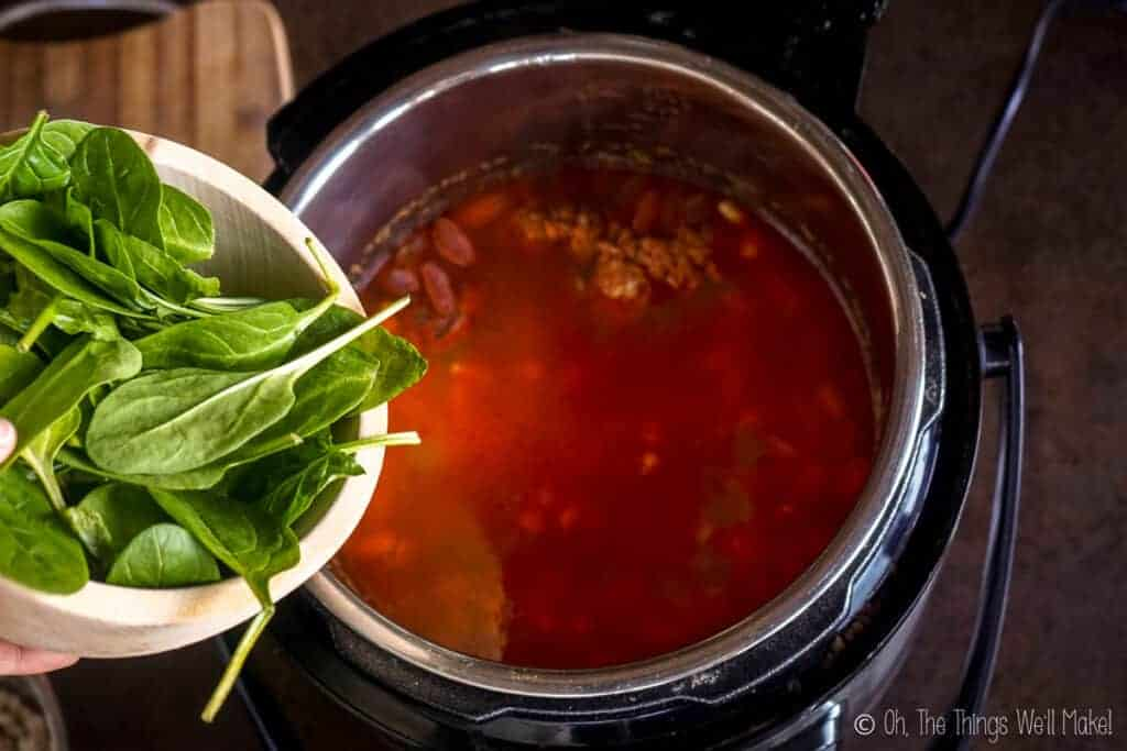 A bowl of spinach by the cooked soup.