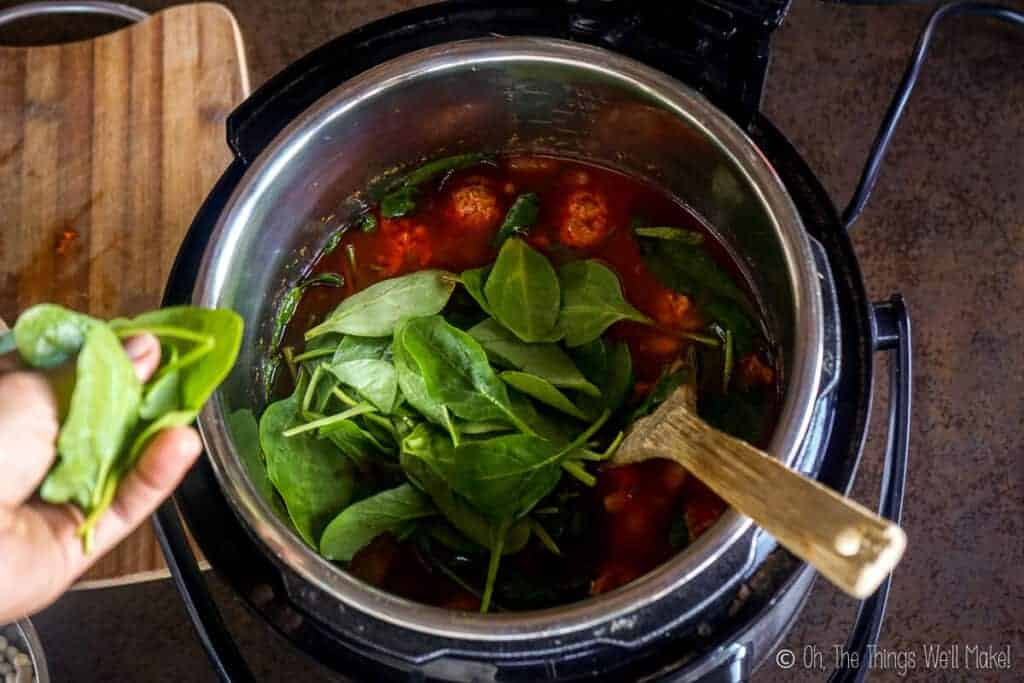 Placing spinach in the cooked soup