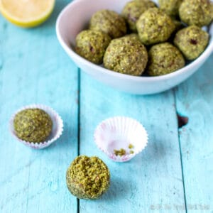 Matcha coconut lime balls in a bowl, with two balls in front of the bowl.