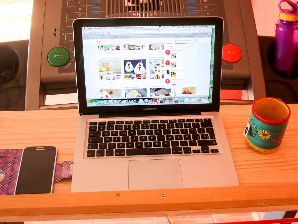 A computer, a phone, and a mug on a removable desk on a treadmill.