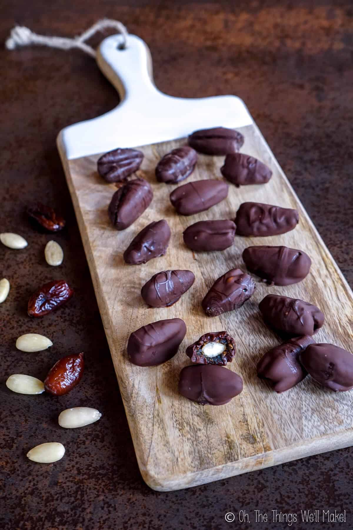 Chocolate dates on a wooden cutting board surrounded by almonds and dates