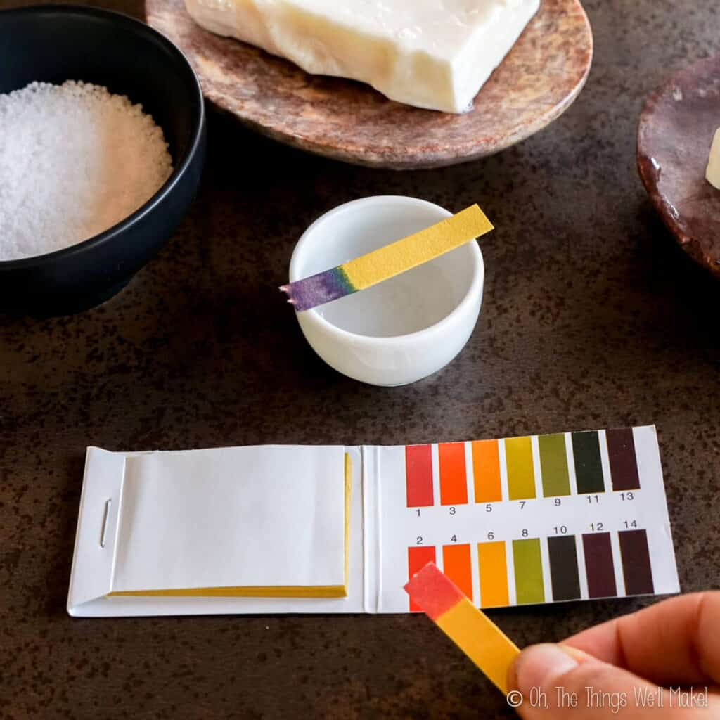 comparing a red pH strip to the pH chart