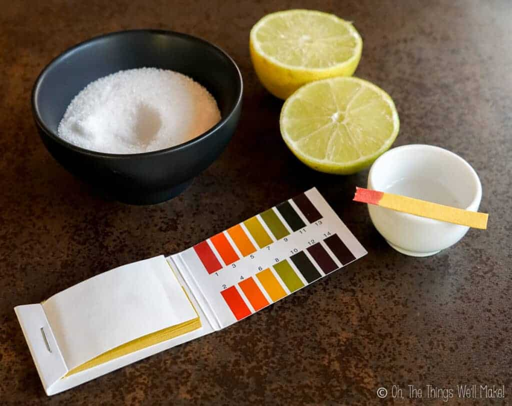 citric acid in a bowl next to a cut lemon and pH test strips