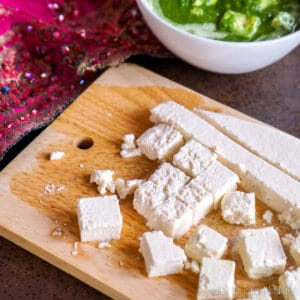 Overhead view of cut cubes of homemade paneer on a bamboo cutting board