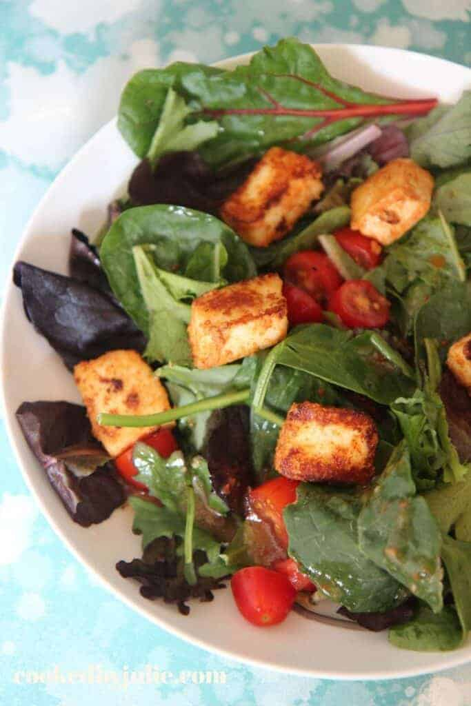overhead view of a salad garnished with fried paneer
