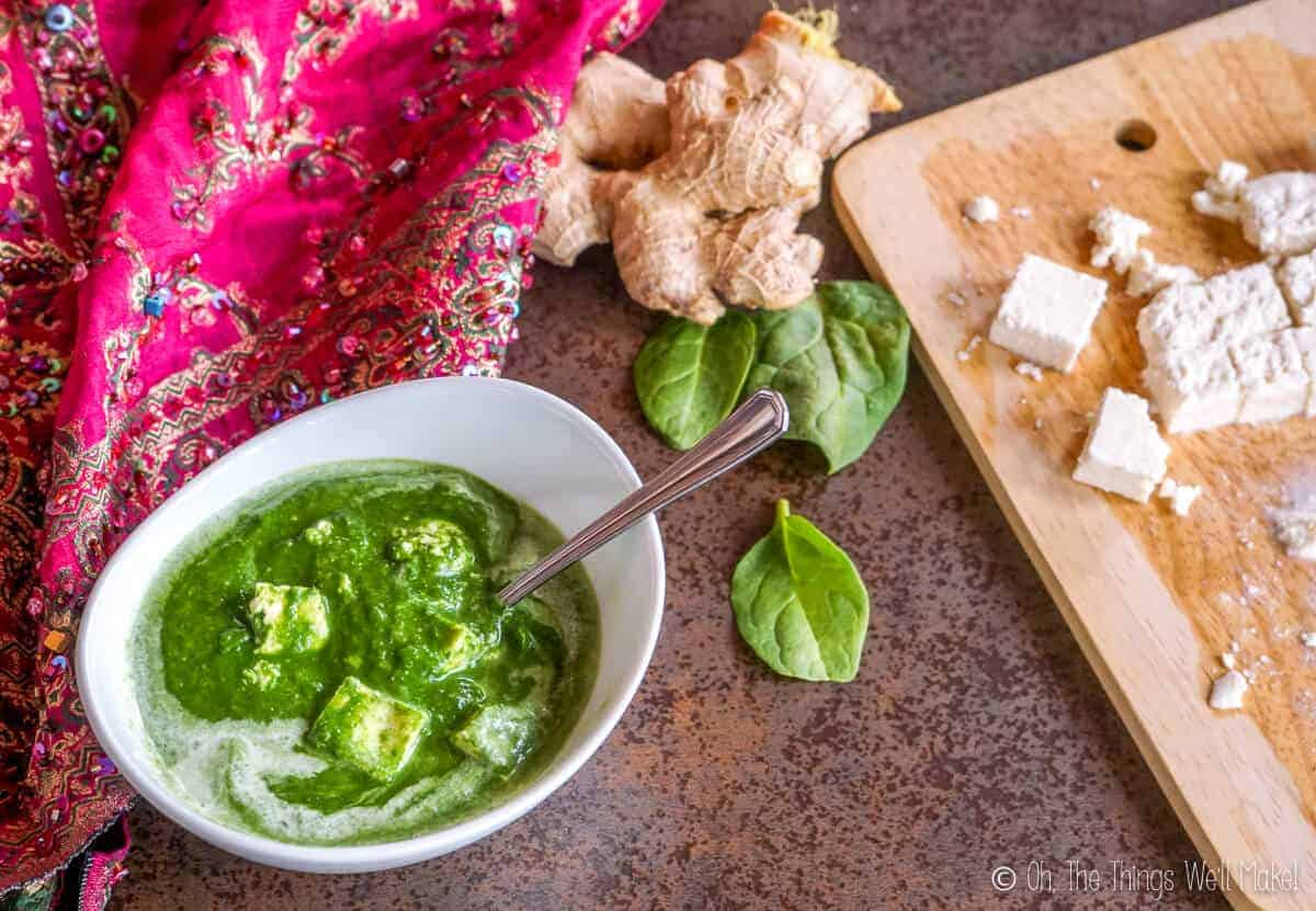 overhead view of palak paneer next to some cut paneer, some fresh spinach leaves, and a ginger root.
