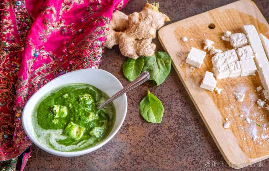a bowl of palak paneer next to some more paneer, fresh spinach leaves, and a fresh ginger root.