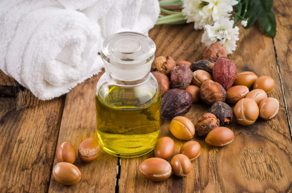 argan oil in a bottle next to argan fruit