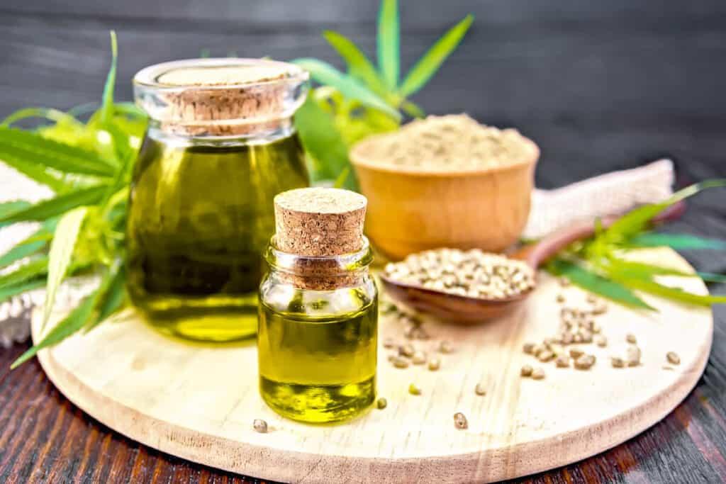 hemp seed oil on a wooden board next to hemp seeds