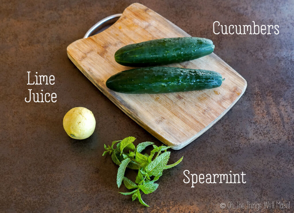 Overhead view of 2 cucumbers, some spearmint leaves, and a small lime.