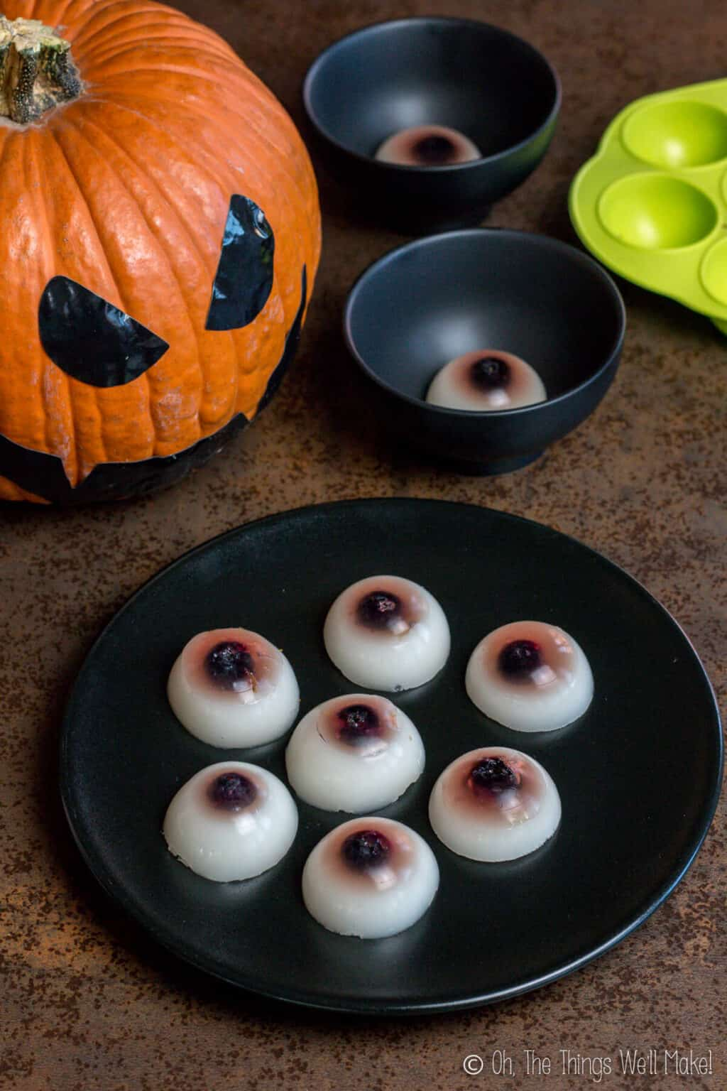 A black plate full of seven gummy eyeballs with a Jack-o-Lantern in the back and several black bowls with one gummy eyeball in them.