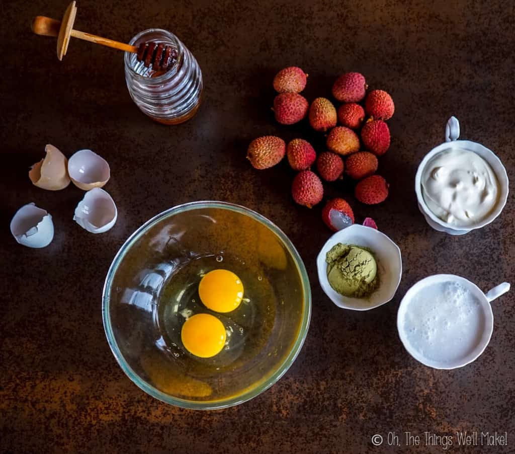 Overhead view of raw eggs in a bowl next to the ingredients for ice cream