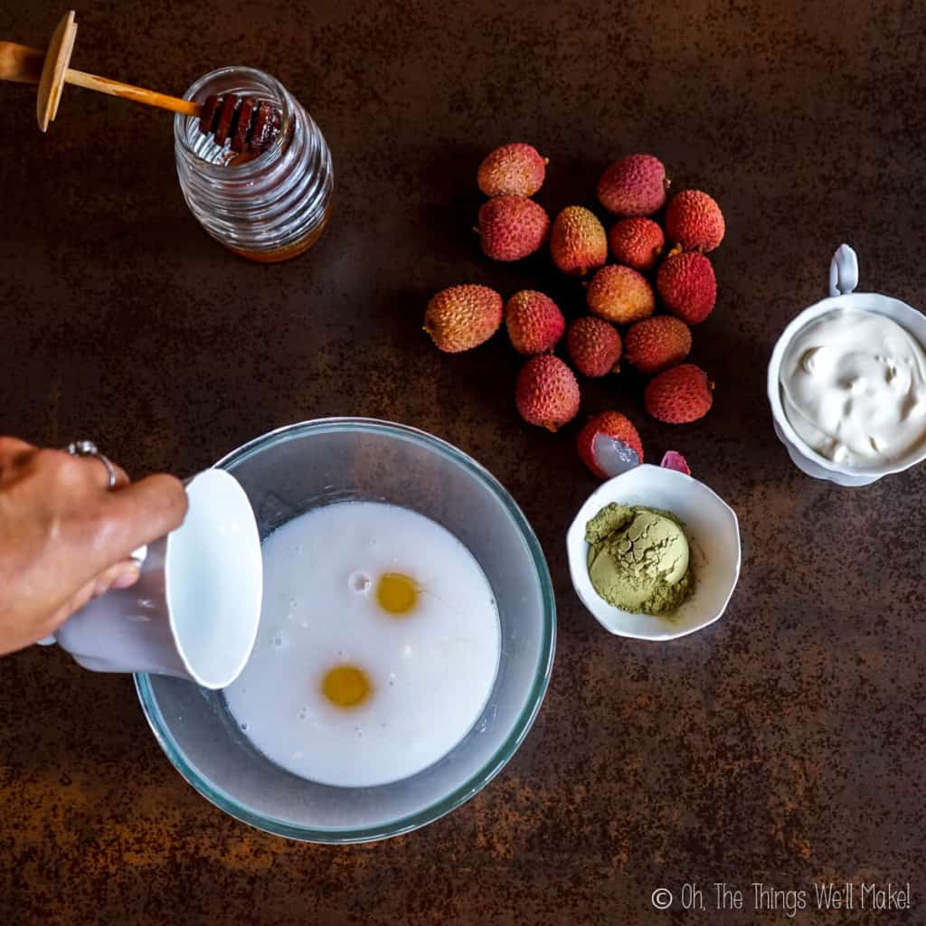 pouring coconut milk into a bowl with raw eggs