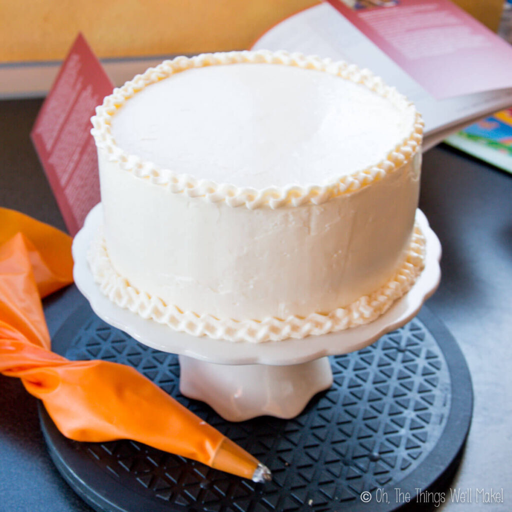 A cake with Swiss buttercream frosting on a cake stand.