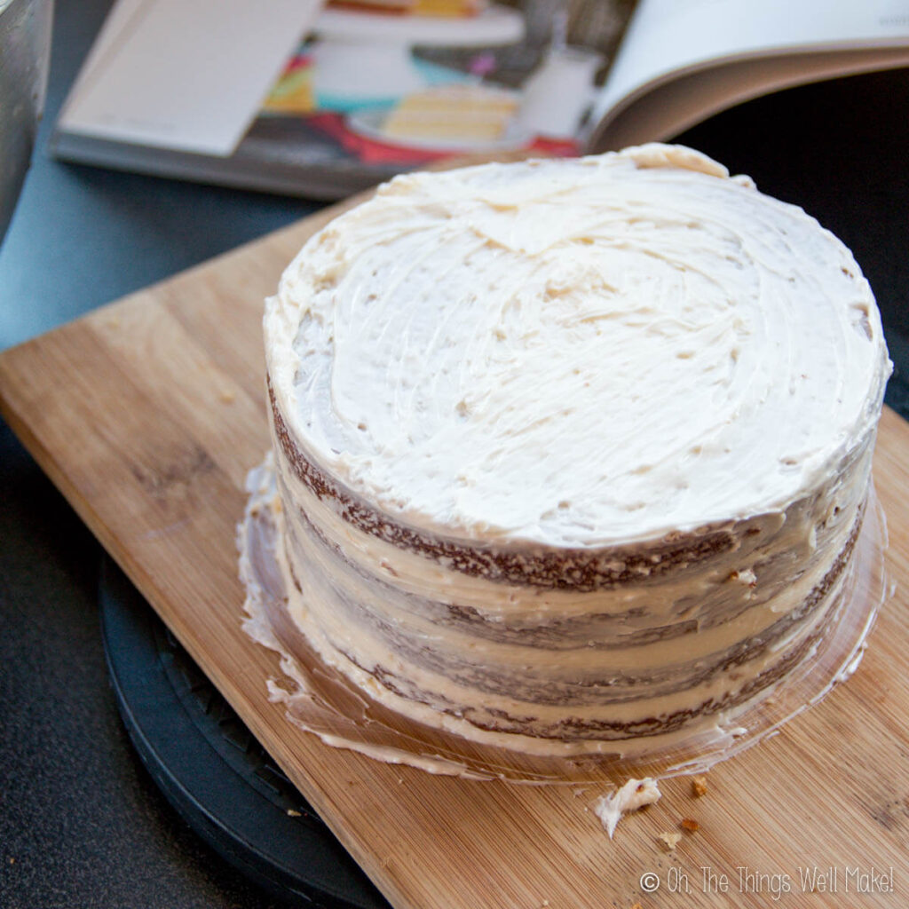 A cake with a thin crumb coat layer of frosting