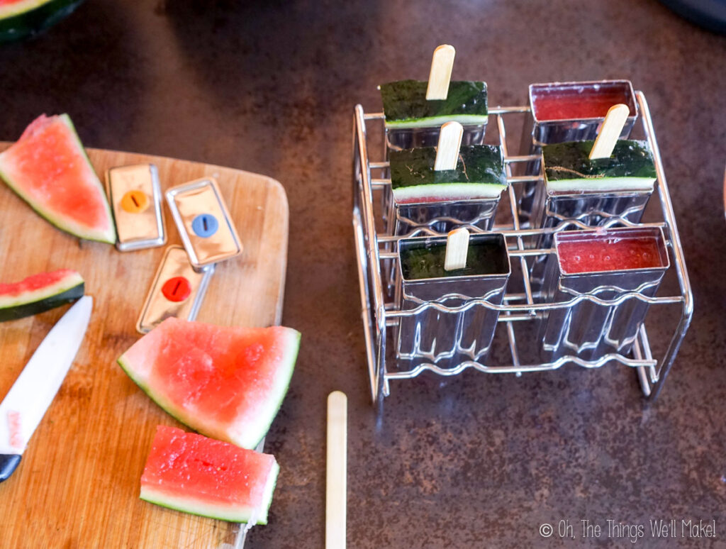 popsicle molds with watermelon rinds holding the sticks in place