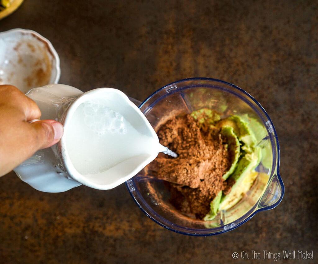 Adding some coconut milk to the blender