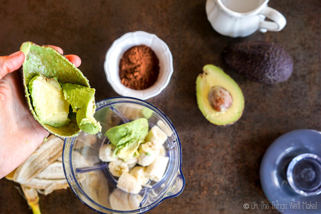 Adding avocado to the blender with the banana chunks