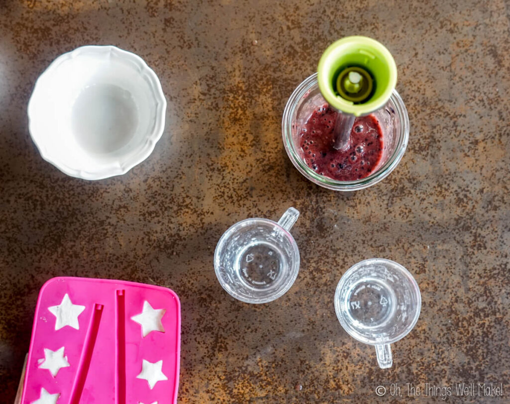 Overhead view of yogurt in star shaped trays and blueberry purée in a glass
